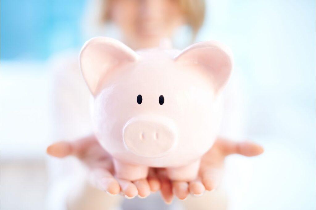 A woman holding a piggy bank